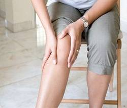 Женщина трет колено при боли