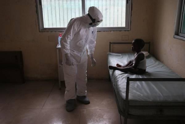 Врач в защитном костюме и черный мальчик больной Эбола